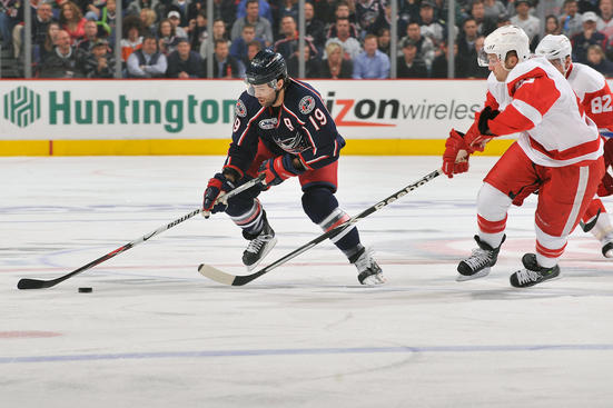 COLUMBUS, OH - APRIL 21:  Michael Peca #19 of the Columbus Blue Jackets skates the puck past Darren Helm #43 of the Detroit Red Wings during Game Three of the Western Conference Quarterfinals of the 2009 Stanley Cup Playoffs at Nationwide Arena April 21, 2009 in Columbus, Ohio.  (Photo by Jamie Sabau/NHLI via Getty Images)