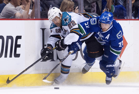 VANCOUVER, CANADA - MAY 1:  Daniel Sedin #22 of the Vancouver Canucks tries to check Dan Boyle #22 of the San Jose Sharks off the puck during the second period in Game One of the Western Conference Quarterfinals of the 2013 NHL Stanley Cup Playoffs, May 01, 2013 at Rogers Arena in Vancouver, British Columbia, Canada.  (Photo by Rich Lam/Getty Images)