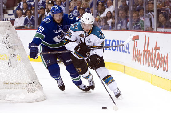VANCOUVER, CANADA - MAY 3:  Alexander Edler #23 of the Vancouver Canucks tries to check Tim Kennedy #46 of the San Jose Sharks off the puck during the first period in Game Two of the Western Conference Quarterfinals of the 2013 NHL Stanley Cup Playoffs, May 03, 2013 at Rogers Arena in Vancouver, British Columbia, Canada.  (Photo by Rich Lam/Getty Images)