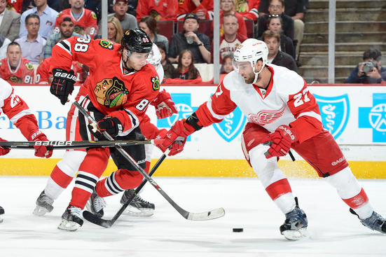 CHICAGO, IL - MAY 15: Patrick Kane #88 of the Chicago Blackhawks and Kyle Quincey #27 of the Detroit Red Wings fight for the puck in Game One of the Western Conference Semifinals during the 2013 Stanley Cup Playoffs at the United Center on May 15, 2013 in Chicago, Illinois. (Photo by Bill Smith/NHLI via Getty Images)