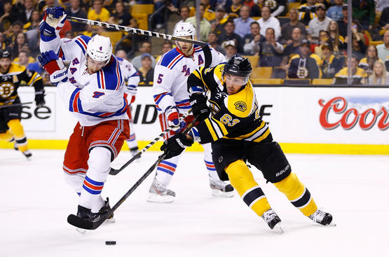 BOSTON, MA - MAY 16:   Brad Marchand #63 of the Boston Bruins carries the puck around Michael Del Zotto #4 of the New York Rangers in the first period in Game One of the Eastern Conference Semifinals during the 2013 NHL Stanley Cup Playoffs on May 16, 2013 at TD Garden in Boston, Massachusetts. (Photo by Jared Wickerham/Getty Images)