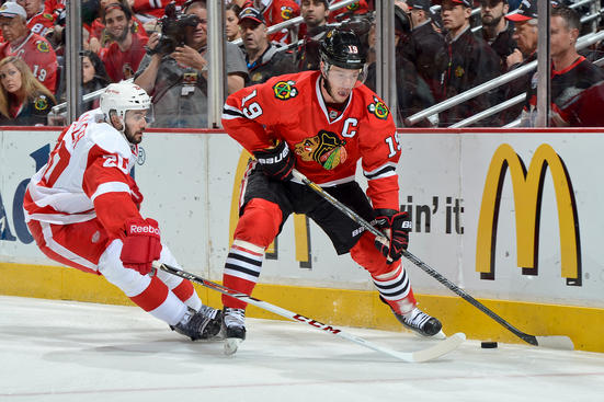 CHICAGO, IL - MAY 29: Jonathan Toews #19 of the Chicago Blackhawks approaches the puck as Drew Miller #20 of the Detroit Red Wings reaches from behind in Game Seven of the Western Conference Semifinals during the 2013 Stanley Cup Playoffs at the United Center on May 29, 2013 in Chicago, Illinois. (Photo by Bill Smith/NHLI via Getty Images)