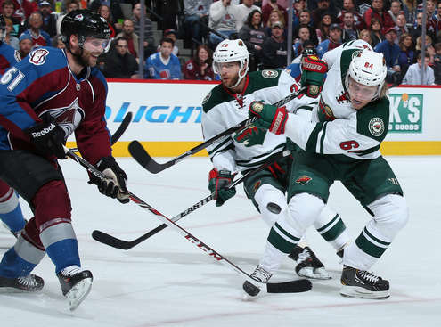DENVER, CO - APRIL 30:  Mikael Granlund #64 of the Minnesota Wild attempts to get a shot off against Andre Benoit #61 of the Colorado Avalanche Game Seven of the First Round of the 2014 NHL Stanley Cup Playoffs at Pepsi Center on April 30, 2014 in Denver, Colorado.  (Photo by Doug Pensinger/Getty Images)