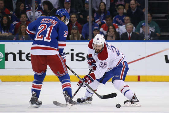 NEW YORK, NY - MAY 29: Josh Gorges #26 of the Montreal Canadiens plays the puck against Derek Stepan #21 of the New York Rangers during Game Six of the Eastern Conference Final in the 2014 NHL Stanley Cup Playoffs at Madison Square Garden on May 29, 2014 in New York City.  (Photo by Bruce Bennett/Getty Images)