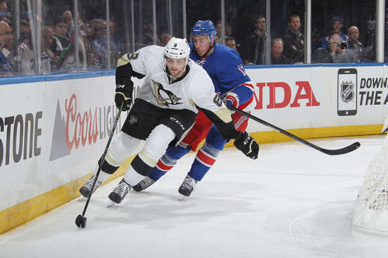NEW YORK, NY - APRIL 18:  Brian Dumoulin #8 of the Pittsburgh Penguins skates with the puck against Kevin Hayes #13 of the New York Rangers in Game Two of the Eastern Conference Quarterfinals during the 2015 NHL Stanley Cup Playoffs at Madison Square Garden on April 18, 2015 in New York City. (Photo by Jared Silber/NHLI via Getty Images)