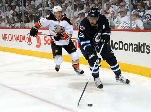 WINNIPEG, CANADA - APRIL 22: Blake Wheeler #26 of the Winnipeg Jets plays the puck along the boards as Cam Fowler #4 of the Anaheim Ducks gives chase during first period action in Game Four of the Western Conference Quarterfinals during the 2015 NHL Stanley Cup Playoffs on April 22, 2015 at the MTS Centre in Winnipeg, Manitoba, Canada.  (Photo by Lance Thomson/NHLI via Getty Images)